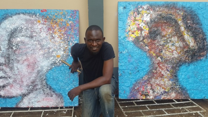 Akinwolere with two of his paintings