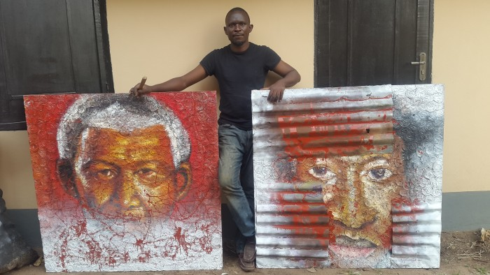 Akinwolere with two of his paintings (titled Fencing} reflecting on leadership in Africa