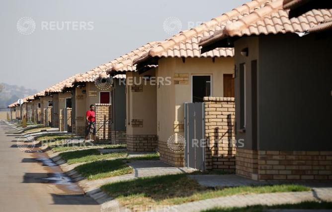 A miner enters a house, part of a 2.8 billion rand ($255 million) housing project put together by her employer at the WaterKlooff Hills in Rustenburg September 16, 2014. Mining companies in South Africa have various social policies they are required to implement but this is the first that strives to give miners a shot at owning middle-class homes that for most would otherwise be beyond their wildest dreams. REUTERS/Siphiwe Sibeko (SOUTH AFRICA - Tags: BUSINESS COMMODITIES REAL ESTATE)