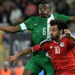 Super Eagles defender, Stanley Amuzie challenges Pharaohs's Muhammed Salah for the ball