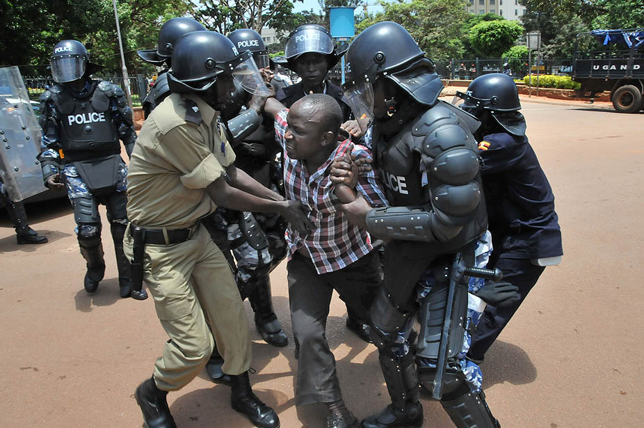 Uganda police detain a supporter of Uganda's top opposition leader Kizza Besigye outside the court in Kampala. Besigye and his co-accused pleaded not guilty Wednesday and were freed on bail, from charges of convening an unlawful assembly in a case stemming from the killing of a policeman in violent street clashes last week. In tense scenes that threatened to turn violent, heavily armed police blocked supporters from following Besigye to the court.