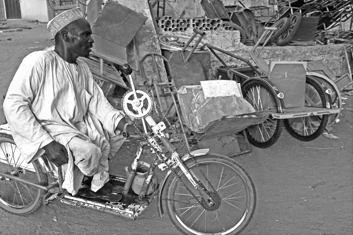 In this Thursday, May 13, 2010 file photo, an unidentified man suffering from polio rides on a make shift bike in Kano, Nigeria.
