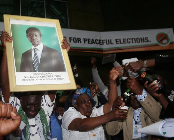 Patriotic Front General Secretary Davies Chama (L) celebrates while holding a portrait of President Edgar Chagwa Lungu after Lungu narrowly won re-election on Monday, in a vote his main rival Hakainde Hichilema rejected on claims of alleged rigging by the electoral commission, in the capital, Lusaka, Zambia, August 15, 2016. REUTERS/Jean Serge Mandela
