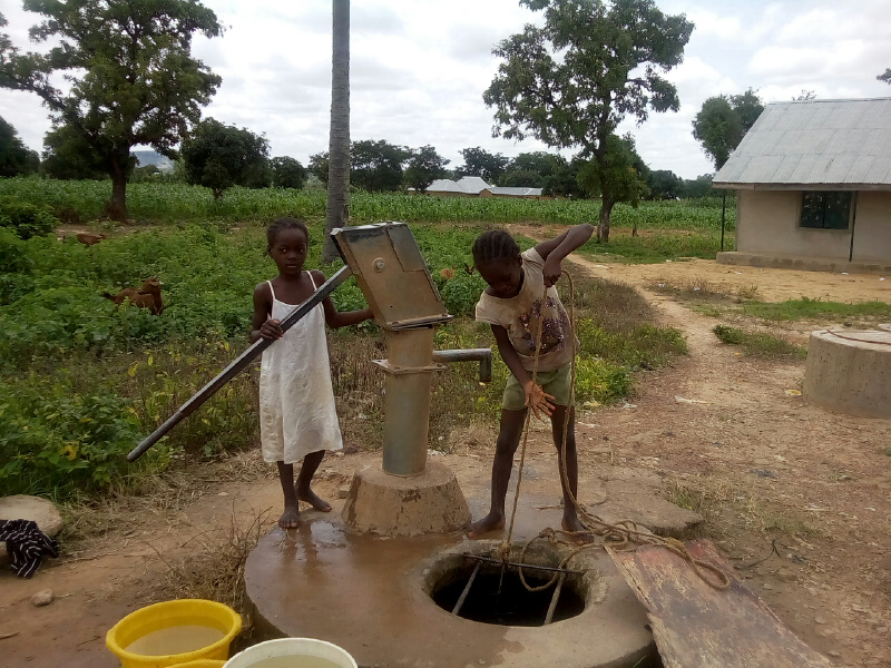 little girls fetching water from the only well in the community