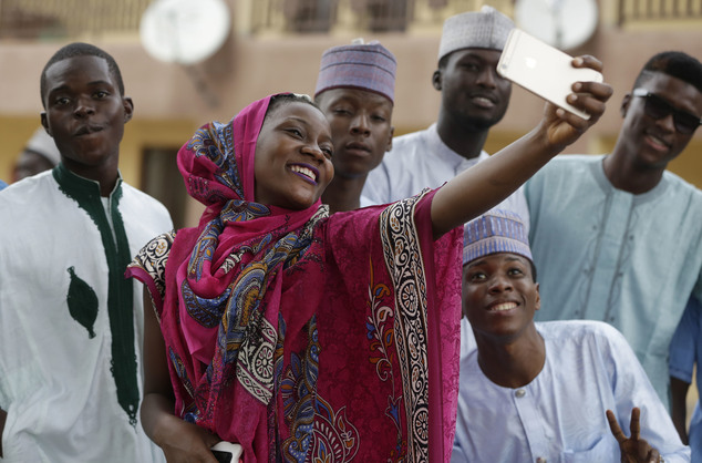 A Nigeria Muslim wpman and friends takes a selfie photo after Eid al-Adha, or Feast of Sacrifice, that commemorates the Prophet Ibrahim's faith, at the prayer ground in Lagos, Nigeria, Monday, Sept. 12, 2016. Eid al-Adha marks the end of hajj. (AP Photo/Sunday Alamba)